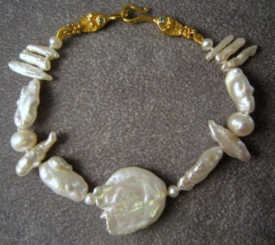Silver bracelet with pearls and hooked fishes